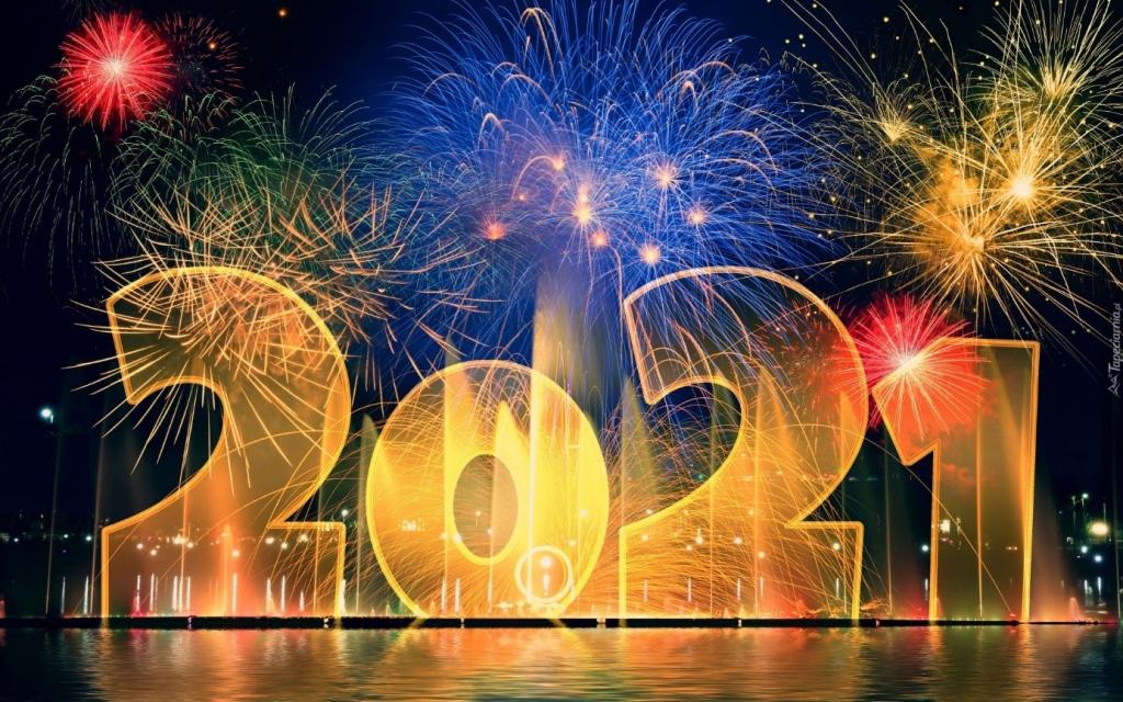 Pocztówka noworoczna. Na granatowym tle nocnego nieba sztuczne ognie a pod nimi złoty napis 2021