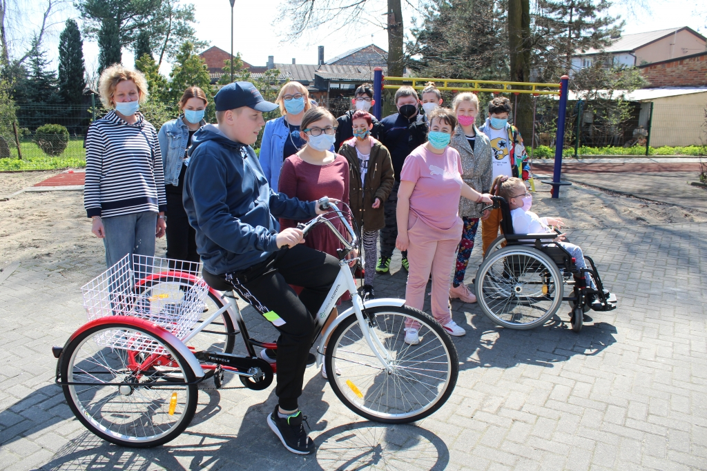 Na zdjęciu jest grupa uczniów Specjalnego Ośrodka Szkolno Wychowawczego w Rychwale wraz z kilkoma nauczycielami. Z nimi w grupie stoi uczeń który otrzymał rower.