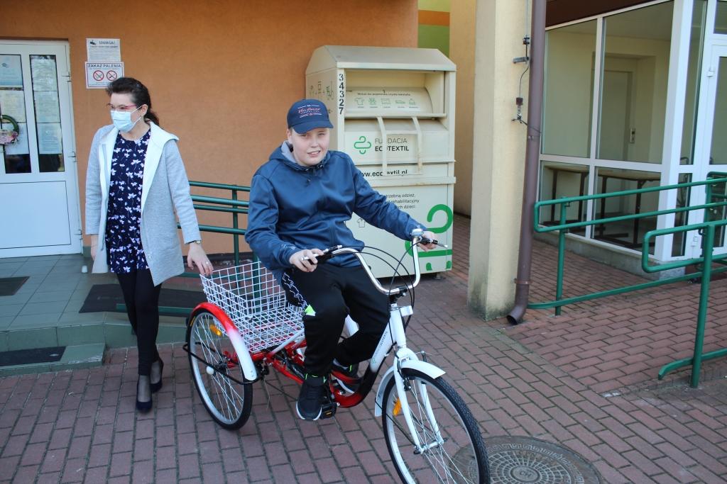 Na zdjęciu uczeń Specjalnego Ośrodka Szkolno Wychowawczego w Rychwale siedzący na otrzymanym rowerze. Z uczniem stoi jego mama, a w tle widoczny jest kontener organizatora akcji i fundatora roweru.
