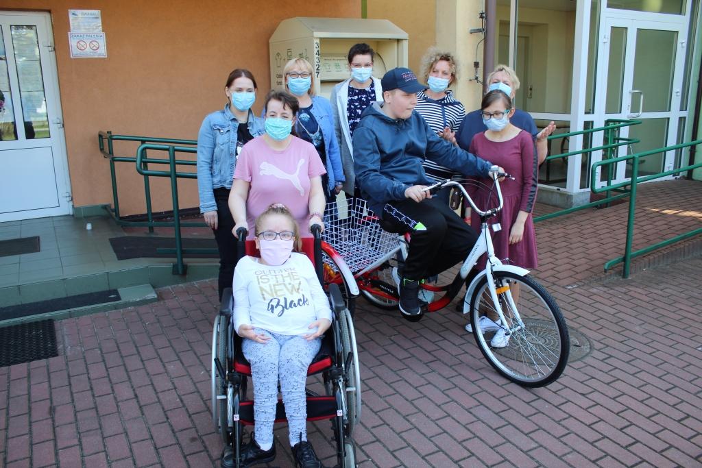 Na zdjęciu jest grupa uczniów Specjalnego Ośrodka Szkolno Wychowawczego w Rychwale wraz z kilkoma nauczycielami. Z nimi w grupie stoi uczeń który otrzymał rower. W tle ustawiony jest kontener na odzież używaną z Fundacji Eco Textil, który jest organizatorem akcji ZRÓB PORZĄDEK W SZAFIE.